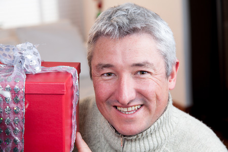 35 40 years old: Happy man holding a gift