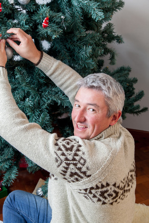 Happy man decorating the christmas tree