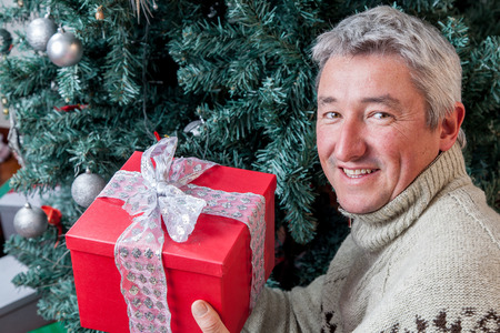 35 40 years old: Man beside the christmas tree holding a red giftbox