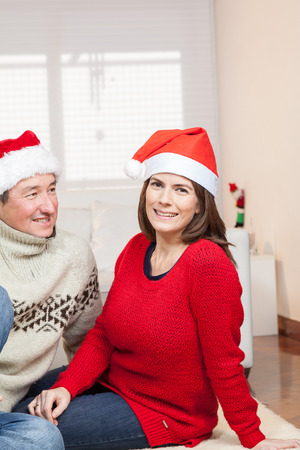 35 40 years old: Couple sitting with hats of christmas