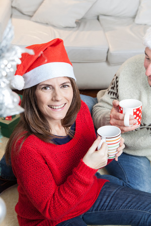 35 40 years old: Woman drinking a cupful of coffee with a hat of christmas