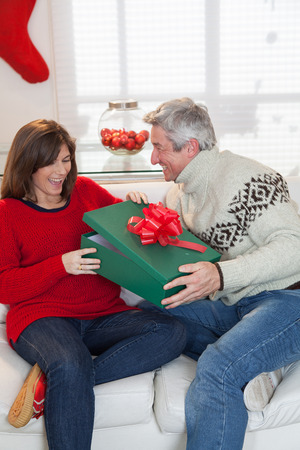 35 40 years old: Woman opening the gift that gives her husband