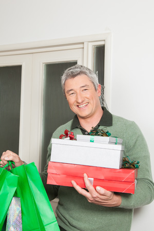 40 year old man: Happy man holding a lot of giftbox