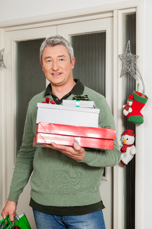 40 year old man: Man holding a lot of giftbox