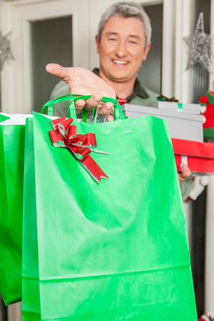 35 40 years old: Man holding a green giftbag with a red bun
