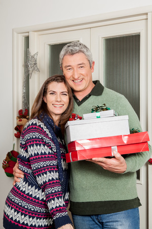 Woman hugging his husband and holding gift bags