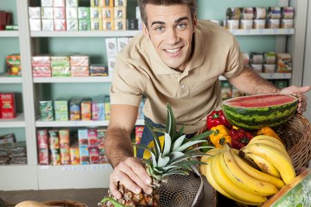 Man looking at camera and choosing the fruit photo