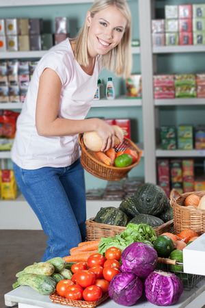 woman s bag: Happy woman buying vegetables Stock Photo