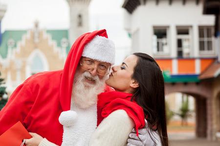 bacio: donna che dà un bacio a Babbo Natale Archivio Fotografico