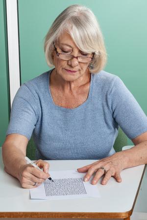 resolving: old woman resolving crossword
