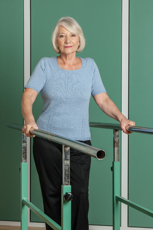 people with disabilities: Old woman using a orthopedic treadmill