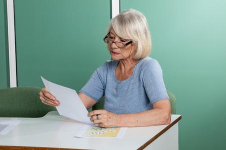 resolving: Elderly woman resolving a croosword