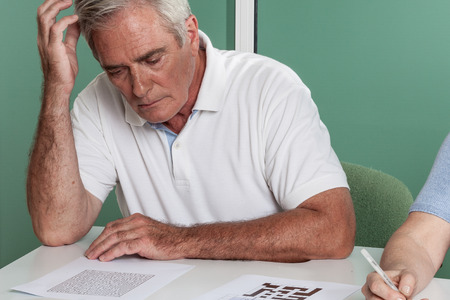 resolving: Elderly man resolving a croosword