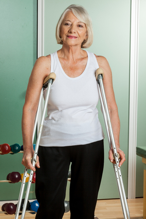 crutches: Old woman walks with crutches Stock Photo