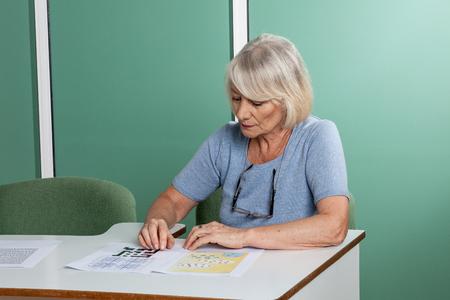resolving: Elderly woman resolving a crossword Stock Photo