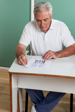 resolving: Uomo anziano risolvere un crooswords