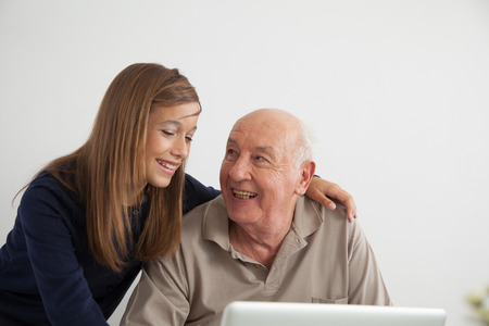 70 75: Portrait of granddaughter teaching computer to her grandfather Stock Photo