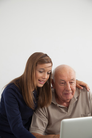 70 75 years: Young girl teaching computer to her grandfather Stock Photo