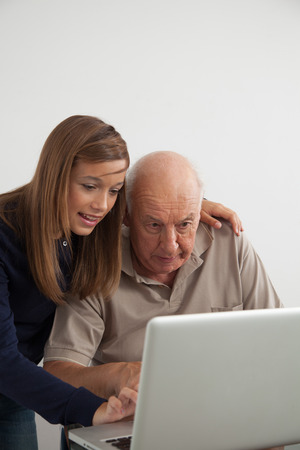 70 75 years: Granddaughter teaching computer to her grandfather