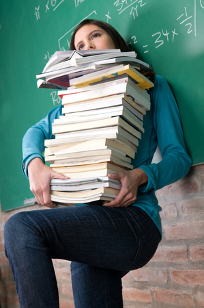 20 25 years old: Woman holding a lot of books Stock Photo
