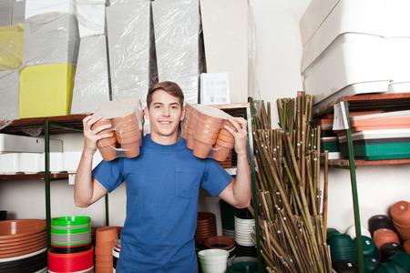 ollas de barro: hombre que sostiene las ollas de barro jóvenes