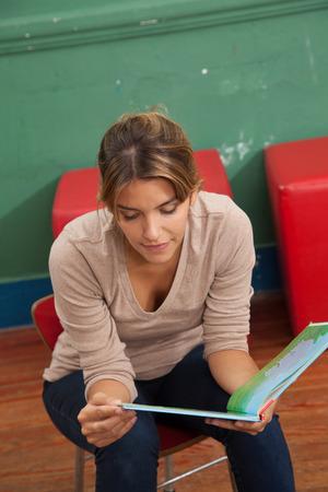 20 year old girl: Teacher reading a book