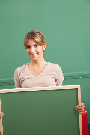20 to 25 years old: Pretty woman holding a blackboard