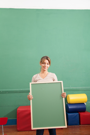 20 25 years: Young woman holding a blackboard