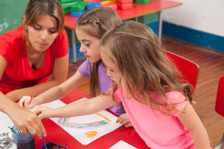 kindergarden: Woman and girls drawing in kindergarden Stock Photo