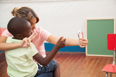 20 to 25 years old: Teacher and african boy take a selfie Stock Photo