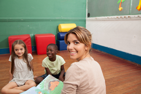 20 year old girl: Teacher and students playing  in kindergarden
