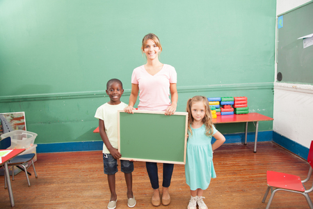 20 year old girl: Teacher and students holding a blackboard
