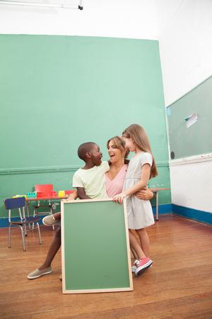 20 year old girl: Teacher and school girl and boy holding a blackboard