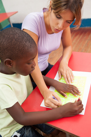 20 year old girl: Woman teaching to her schoolboy
