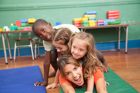 20 year old girl: Teacher and students have fun in kindergarden