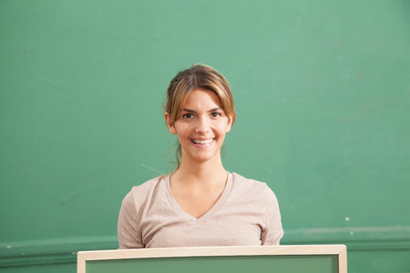 20 25 years old: Young woman holding a blackboard