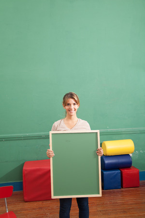20 to 25 years old: Young woman holding a blackboard