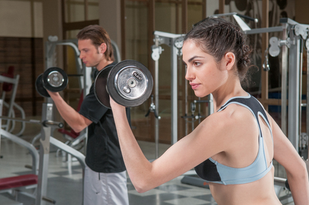 20 30 years: Man and woman lifting weights