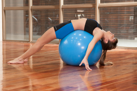 20 30 years: woman exercising on a blue ball