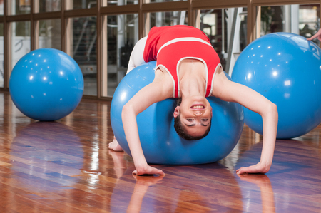 20 30 years: Woman exercising with a blue ball Stock Photo