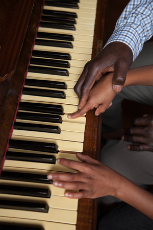 Father teach to his daughter playing piano
