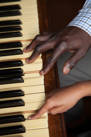 Black man and girl playing piano