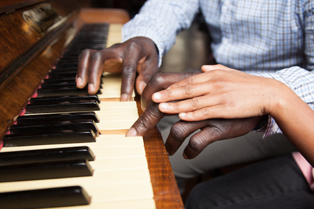 Black girl and father playing piano