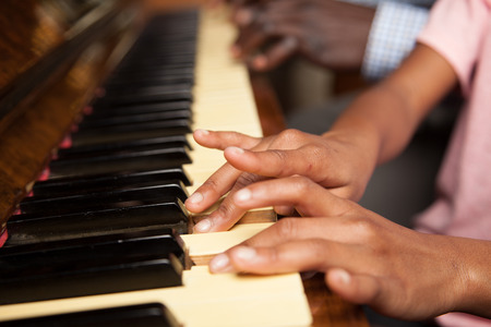 Black father teach his daughter to play piano