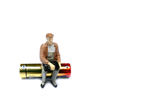 9v battery: Miniature man sitting on AA battery isolated on white with room for copy space Stock Photo