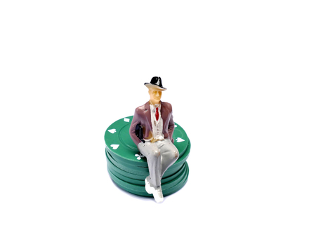 stake: Miniature man sitting on poker chips isolated on white with room for copy space, gambling concept Stock Photo