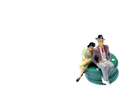 mini job: Miniature man and woman sitting on poker chips isolated on white with room for copy space, gambling concept
