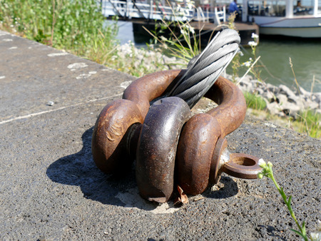 cast off: Old and rusty mooring ring with braided steel cable docked ship in background Stock Photo