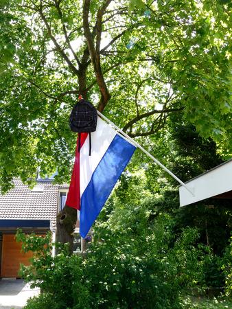 dutch: Dutch tradition school bag on flag When graduating