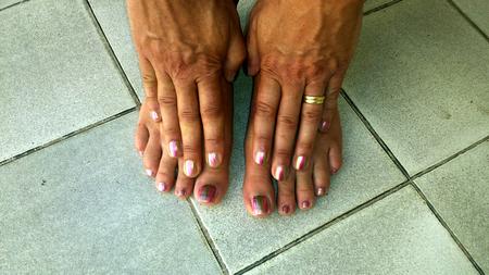 nailpolish: Toes and fingers with bi-color nailpolish on tile floor Stock Photo